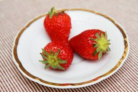 Red strawberry on a white plate