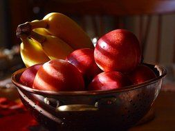 nectarines and bananas in a bowl