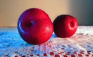 two red plums on the table close-up
