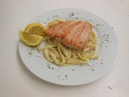pasta with salmon on a white plate