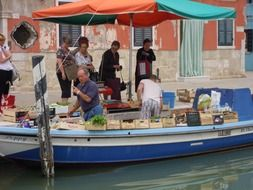 vendor in boat with vegetables on street market, italy, venice