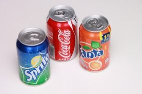 can of coca cola, can of sprite and fanta