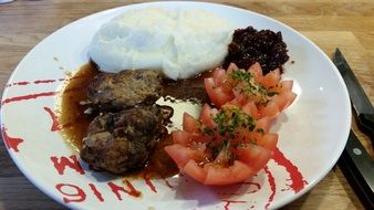 Mashed potatoes,tomatoes and meat on the plate