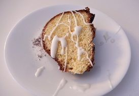 orange cake with icing sugar on white plate