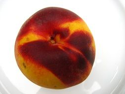 ripe peach on a white plate