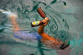 a young man under the water is holding two beer bottles