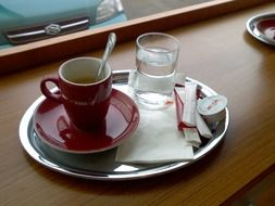 coffee in red cup and water in glass on metal plate