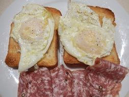 fried eggs, white bread and salami