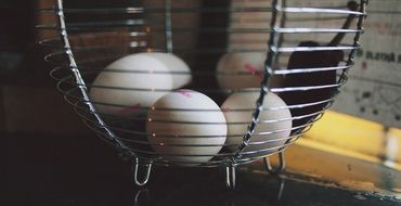 white chicken eggs in a metal basket