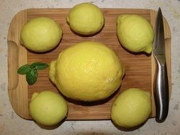 six yellow lemons on a cutting board
