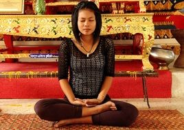 young thai woman meditating in a buddhist temple