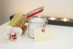 white body cream and scrub brush with a gift card