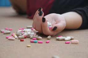 woman holding hundreds of colourful pills