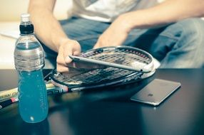 A tennis racket, a bottle of drink and a mobile phone on the table