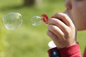 child making soap bubbles
