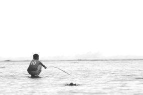 black and white photo of a boy fishing