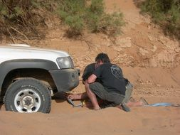 two men preparing car for towing in desert