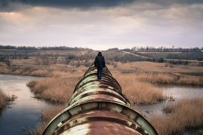 person walking metal pipeline river view
