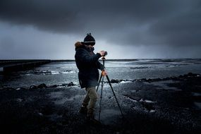 photographer with a camera on a tripod during bad weather