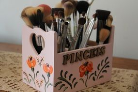 set of makeup brushes in a wooden stand