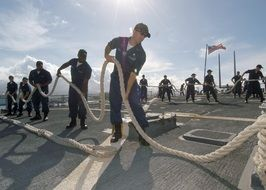 teamwork, navy sailors with ropes on desk of aircraft carrier