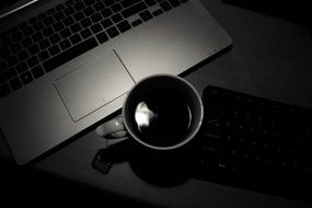Black and white photo of office desk with laptop and cup of coffee