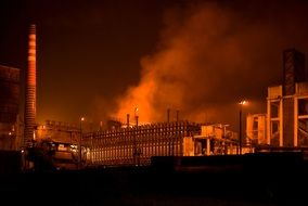smoke over an industrial factory at night