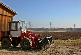 Tractor near a wooden shed