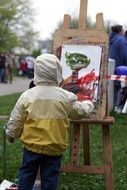 child boy painting bright figure in park