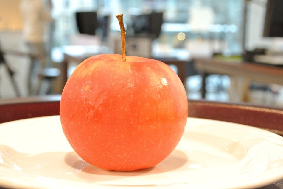 a side view of an apple with a tail