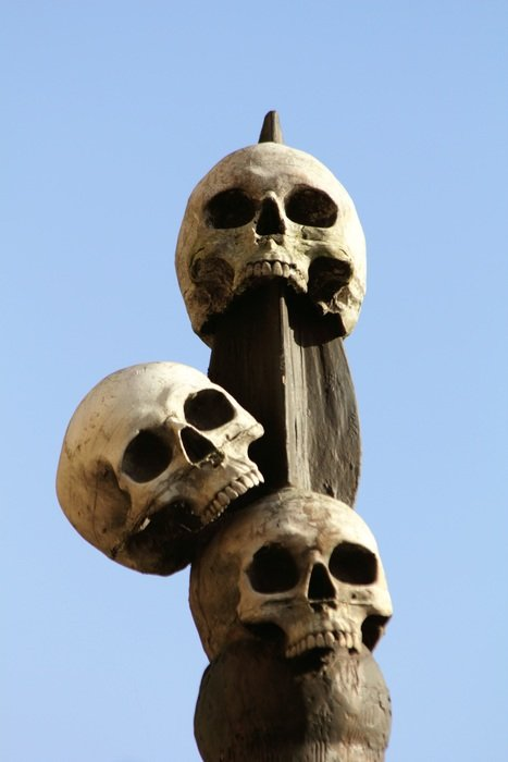 three skulls which is hanging on a pillar