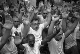 black and white photo of men with hands up