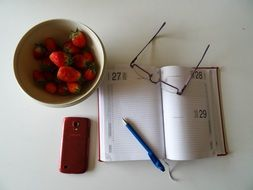 strawberries and notebook on a table