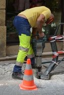 Worker with a drill performs roadworks
