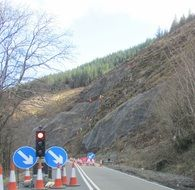 traffic signg, cones and lights on road, roadworks at hillside