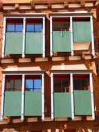 windows with green mechanical shutters on wooden facade