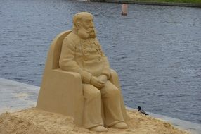 sand statue of a man in an armchair