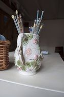 knitting needles in a jug on the table
