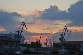 cranes in port at evening sky