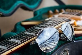 sunglasses lie on the guitar