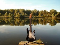 Standing electric guitar on a river bank