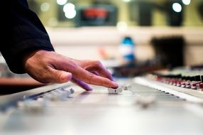 human hands on mixing console