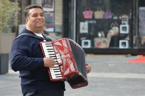 man playing piano accordion street view
