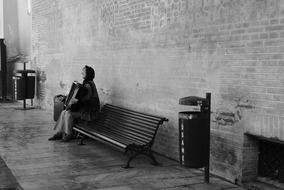 black and white photo of a street musician on a bench