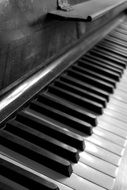 Side view of black and white piano keys in black and white background