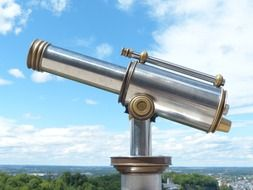 Telescope against a blue sky with clouds