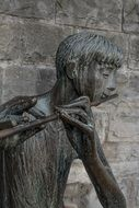 bronze statue of a boy with flute