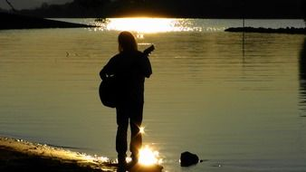 silhouette of a guitar player on sunset background