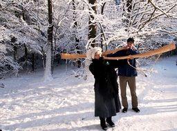 men carry a musical horn in the winter forest