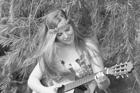 black and white image of a girl who plays the guitar